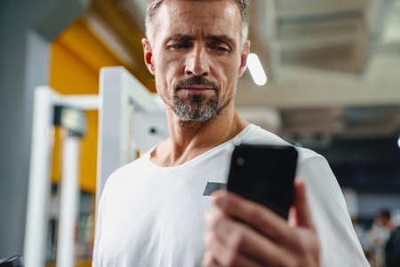 Handsome young man with smartphone in gym