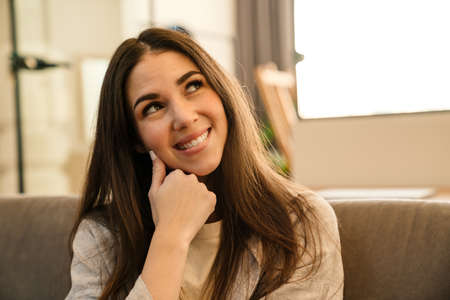 Happy young woman smiling and looking upward while sitting on sofa indoors