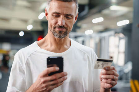 Handsome smiling young man with smartphone in gym, shopping online with credit card