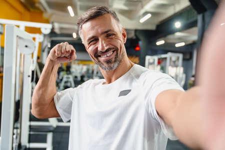 Joyful grey adult sportsman showing his bicep while taking selfie photo in gym