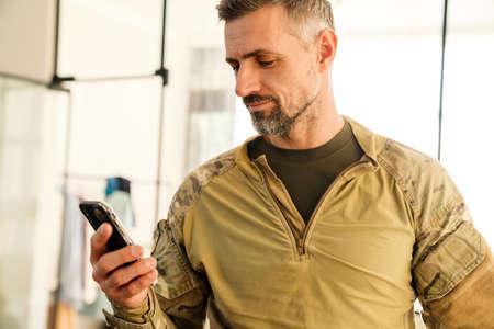 Pleased masculine military man using mobile phone indoors 版權商用圖片