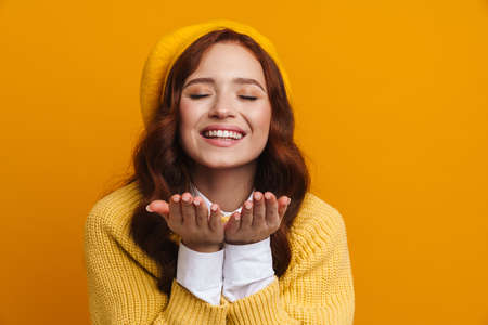 Happy young woman with long red hair in sweater and beret standing over yellow wall background, sending love kiss