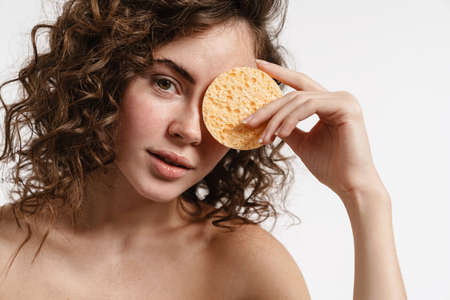 Beautiful shirtless girl posing with cosmetic sponge isolated over white background
