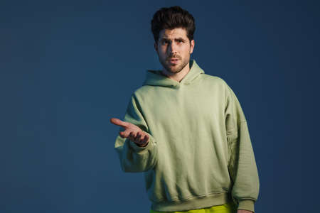 Perplexed handsome man in sportswear posing and gesturing at camera isolated over blue background