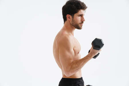 Half-naked athletic sportsman working out with dumbbell isolated over blue background Foto de archivo