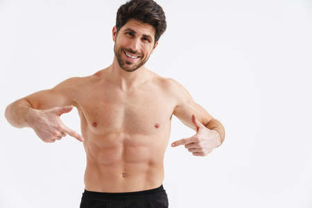 Shirtless joyful sportsman pointing fingers at his abs isolated over white background