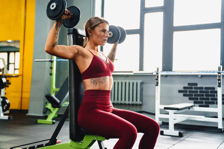 Image of strong young woman fitness coach making sport exercise for arms with dumbbells in gym