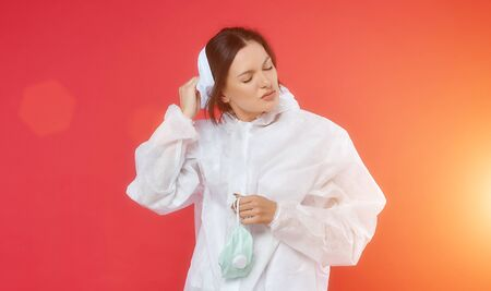 female doctor in a chemical suit. remove the protective mask after work