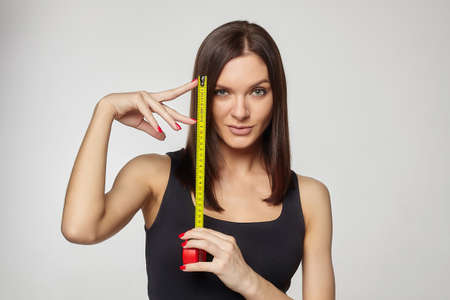 beautiful girl holds a measuring tape in her hands. the concept of imagination about the size of the penis ...