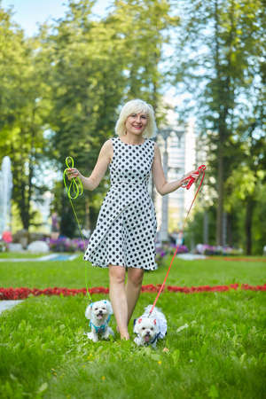 adult woman in the park with two Maltese lapdogs.