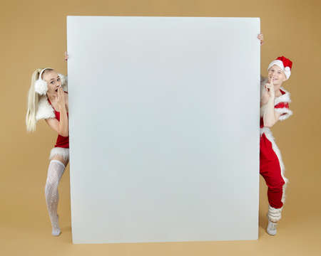 guy and girl in Santa costumes at a photo shoot in the Studio. guy puts Christmas decorations on a girl