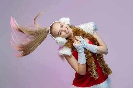 young girl in a Santa Claus costume covered one eye with Christmas decorations with a smile