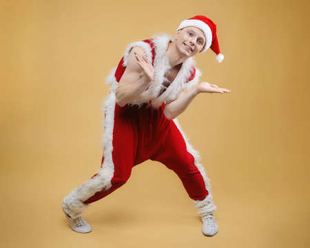 young guy dancer in a Santa suit on a yellow background