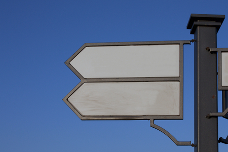 metal pole: Signpost. Index path, located on the pole. Black metal pole. Arrows with a white field for writing. Against the background of the blue sky.