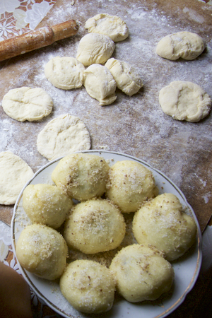 billet: The process of preparation of Ukrainian dumplings. Plate with dumplings and ready for new billet located on the work surface. Dough, flour and tools lying on a cutting board.