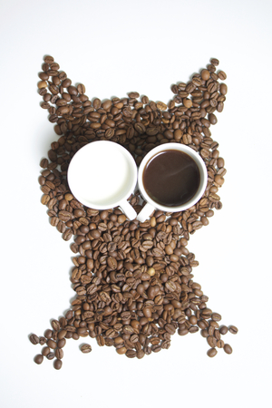Roasted grains of black coffee. The grains are scattered in the form of an owl figurines. Owl Eyes in the form of two white cups. One of them poured brewed coffee. In another milk. Stock Photo
