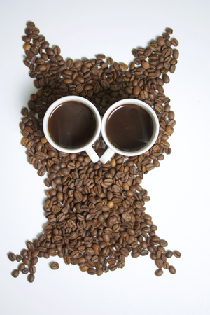Roasted grains of black coffee. The grains are scattered in the form of an owl figurines. Owl Eyes in the form of two white cups of brewed coffee is poured into them. Stock Photo