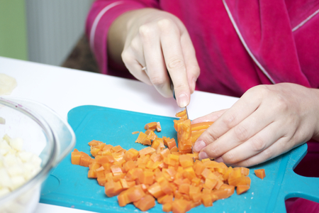 ensaladilla rusa: Vegetable salad. Russian recipes.  Cooking Stages. Woman slices boiled carrot into cubes. A kitchen knife on a cutting board. Nearby stands a container of preparing a salad. Foto de archivo