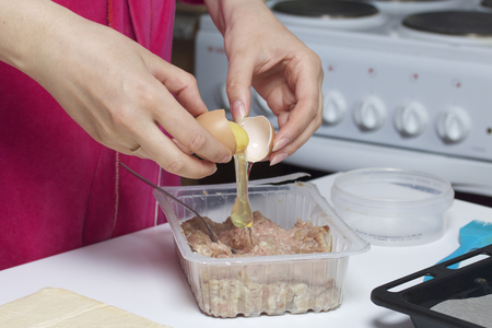 adds: Stages of preparation of meat glomeruli. The woman adds a chicken egg to the stuffing. Next to the table is a dough and tools. Stock Photo