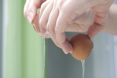 adds: Preparation of biscuit rolls. Stages of preparation. Adding ingredients. A woman adds an egg.