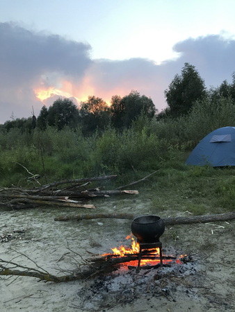 Twilight in the tourist camp. A diluted fire. A pot of cooked food standing on the fire. Tent camp on the river bank.