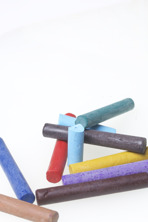 Crayons pastels in different colors. Lying in a box in their places. On a white background. In a chaotic order.