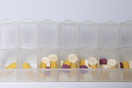 Tabletten en pillen worden op de dagen van de week in een container voor tabletten verdeeld. Geneesmiddelen van verschillende vormen en kleuren. Stockfoto