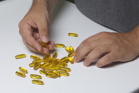 De man verzamelt pillen met gele kleur van de tafel. Stockfoto