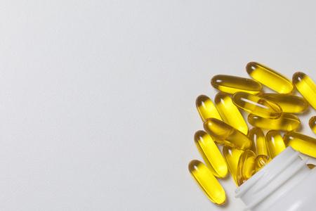 Pillen van gele kleur worden op een wit oppervlak van plastic potten gegoten. Uitzicht vanaf boven.