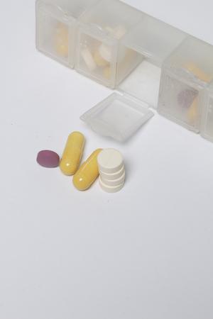 Een dagelijkse dosis tabletten ligt in de buurt van een speciale container voor dagelijkse medicatie. Eén cel voor deze dag is open, tabletten er naast liggen naast elkaar. Stockfoto