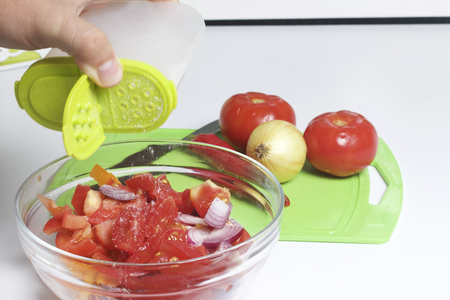 adds: A set of vegetables for salad lies near the cutting board. The man adds salt.