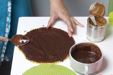 A woman smeared with chocolate wafer cakes. Waffle cake with boiled condensed milk and chocolate. Cooking process. Wafer cakes, cocoa and condensed milk are the ingredients for cooking. Stock Photo