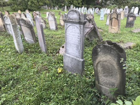 TERESVA, UKRAINE, SEPTEMBER 18, 2017; An old Jewish cemetery. Shattered gravestones stand among the green grass. On them - inscriptions in Hebrew.