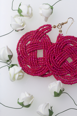 Female earrings of coral color. Hand made of beads. Artificial roses are beige for decoration. On a white background.