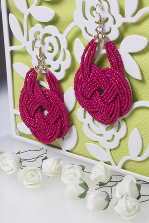 Female earrings of coral color. Hand made of beads. Artificial roses are beige for decoration. Stock Photo