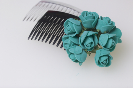 Hair care. Accessories and decorations. Two scallops for hair are transparent and black in color. Artificial rose flowers are emerald for interweaving or decorating. On a white background.