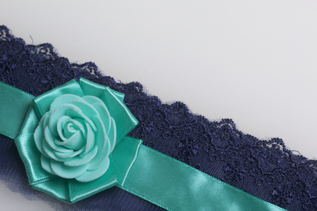 Decoration on hand in the form of a rose of emerald color, sewn to a satin ribbon. On a white background.
