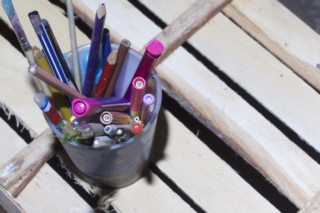 A glass with pencils, felt-tip pens and handles stands on a floor made of wooden boards.