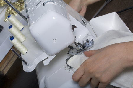 The woman is working on the product on the overlock. Overlock with white thread. The woman directs the cloth clamped in the claw of the overlock.