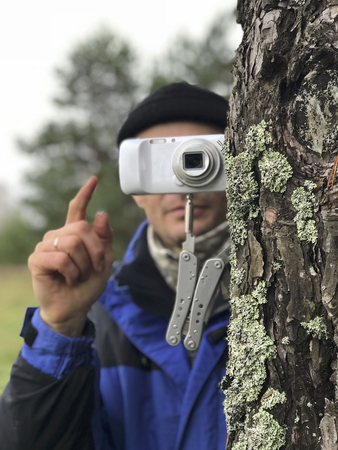 Photographing using improvised means. A compact camera is mounted on a folding knife, stuck stuck in the trunk of a tree instead of a tripod. The photographer controls the camera.