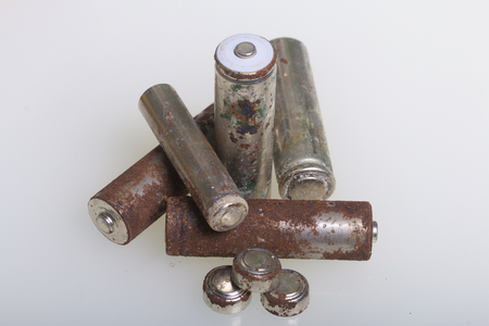 Batteries of corrosion of various shapes and sizes. Lies loose on a white background. Environmental protection, recycling of used batteries. Stockfoto