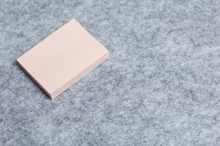 A stack of paper stickers lies on a light gray felt background.