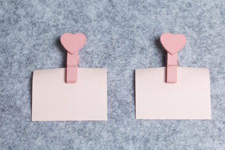 Paper stickers fixed with wooden clothespins with hearts lie on a light gray felt background.