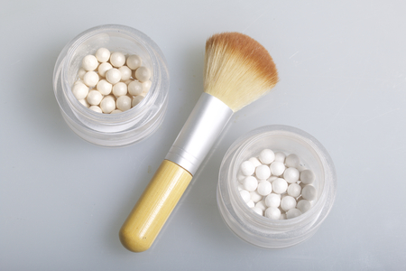 Golden and pearl highlighter in the form of balls in an open jar. Next to it is a cosmetic brush for applying it. On a dark background, view from above.