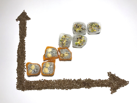 On the white surface, a coordinate axis is plotted with flaxseed. An ascending chart is laid out of sweets. Stock Photo