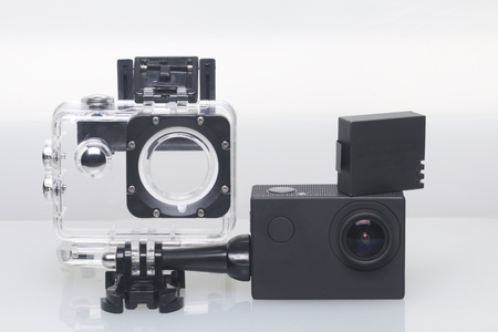 The action camera lies on a white surface. Near the box for underwater shooting and a spare battery.