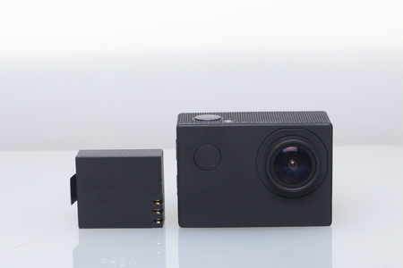 The action camera lies on a white surface. Near the spare battery.