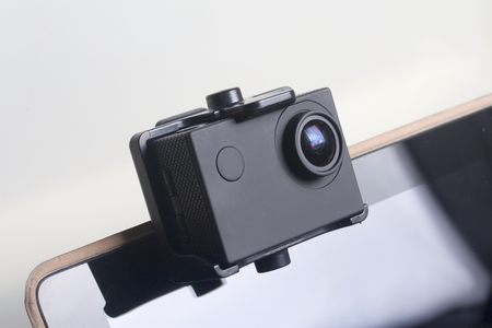The action camera is fixed on the tablet. On a white background.