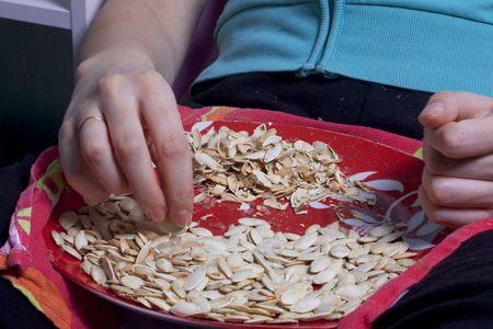 The girl is eating pumpkin seeds. Seeds lie on a plate, next to it lies the husks. Stockfoto