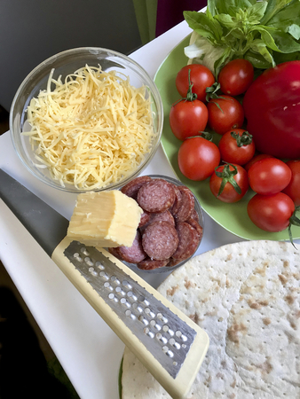 Preparation of pizza. Necessary ingredients are on the table: cheese, sausage, pizza base and vegetables. Stock Photo